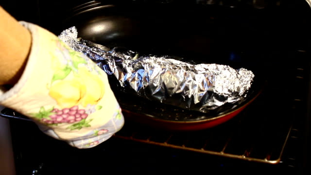 fish with a lemon in a foil is baked in an oven. - aluminum foil stock videos & royalty-free footage