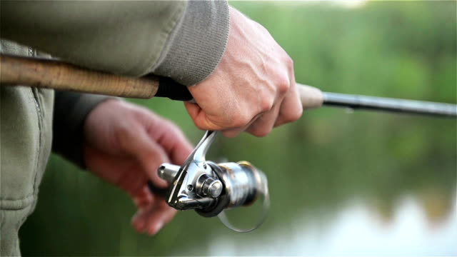 Fisher Man Mishing Over the Lake in the Spring. Angler Holds Fishing Rod. Coil is Seen in a Close Up Fisher Man Mishing Over the Lake in the Spring. Angler Holds Fishing Rod. Coil is Seen in a Close Up. HD fishing rod stock videos & royalty-free footage