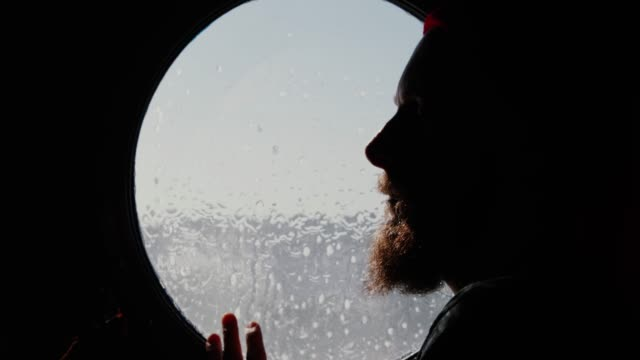 Fisherman at the porthole window of a vessel sailing the sea