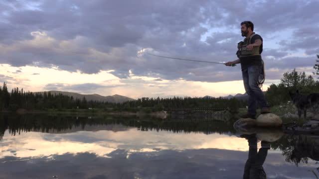 stockvideo's en b-roll-footage met visser afgietsels lijn in meer met bergen in de verte - alleen één mid volwassen man