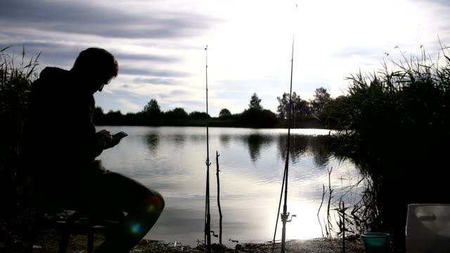 fiskare fångar en fisk och använda telefonen - meta bildbanksvideor och videomaterial från bakom kulisserna