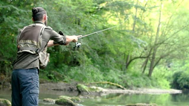 Fisherman catching fish in river Fisherman catching fish in river fishing rod stock videos & royalty-free footage