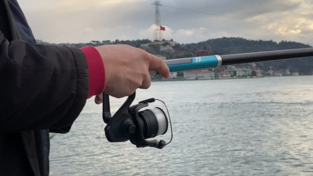 A fisherman hunting in the Bosphorus. He wraps the fishing rod. A fisherman hunting in the Bosphorus. He wraps the fishing rod. fishing rod stock videos & royalty-free footage