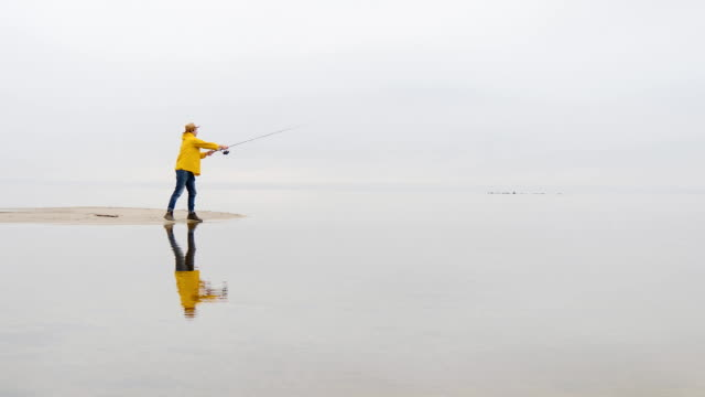 fisherman in yellow raincoat throws fishing tackles with spinning rod in slow motion - wędkarstwo filmów i materiałów b-roll