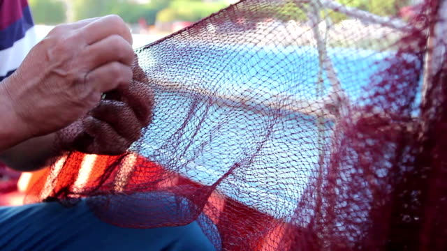 Fisherman is repair the fish net Needle with thread in fisherman mouth until repairing net for angling. wire mesh stock videos & royalty-free footage