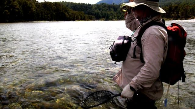fischer, die verrechnung einer bachforelle - süßwasserfisch stock-videos und b-roll-filmmaterial