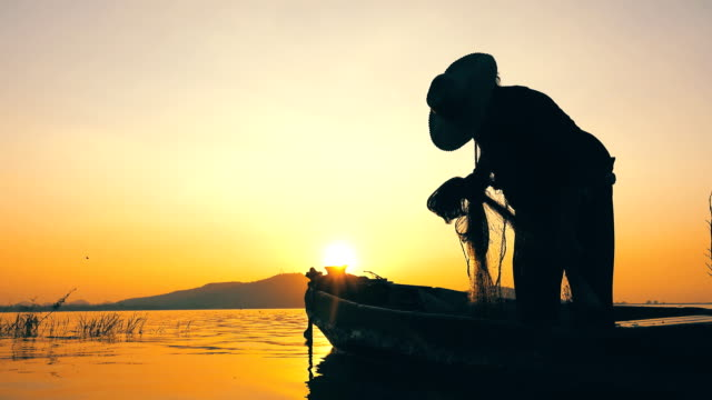 Fisherman on longtail boat fishing at sunset in Thailand