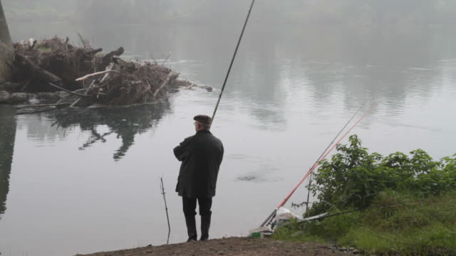 Fisherman on river side in autumn video