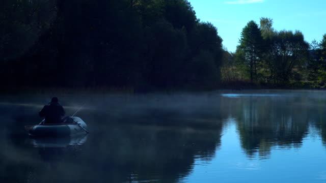 霧の湖でボートに乗って漁師 - 漁師 外人点の映像素材/bロール