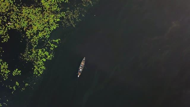 fisherman on the boat on the sunrise aerial - дикая местность стоковые видео и кадры b-roll