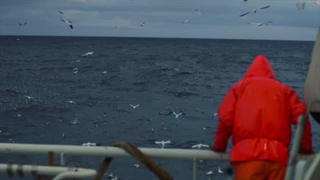 fisherman on the deck of a fishing boat in a stormy sea - rybak filmów i materiałów b-roll