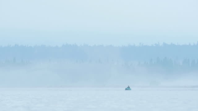 Fisherman on the foggy forest lake. video