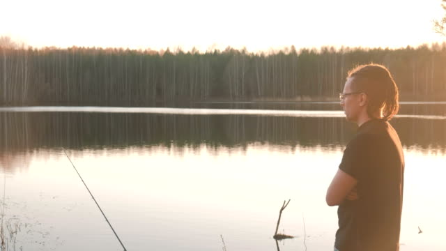 fisherman on the pond. a young guy with dreads in glasses in a t-shirt fishing fish rod. - żabnicokształtne filmów i materiałów b-roll