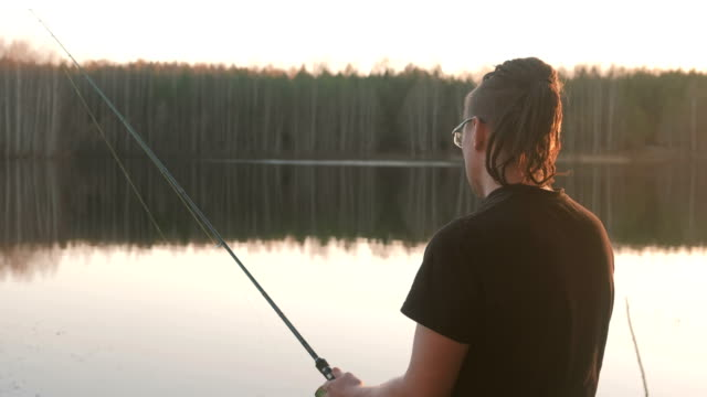 fisherman on the pond. young guy with dreads in glasses in a t-shirt fishing fish with rod. - żabnicokształtne filmów i materiałów b-roll
