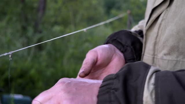 fiskaren sätter maskar som bete till fisken på kroken staven - meta bildbanksvideor och videomaterial från bakom kulisserna