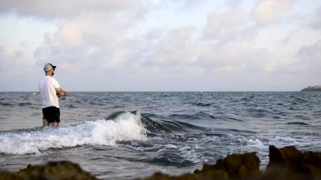 Fisherman standing at the seashore hooks a fish Fisherman standing at the seashore spin fishing hooks a fish fishing rod stock videos & royalty-free footage