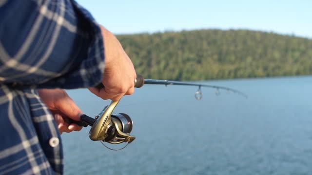 fisherman standing on riverside and trying to catch fish - rybak filmów i materiałów b-roll