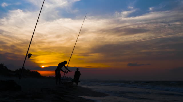 Fisherman using fishing rod for catch fish in sea on beautiful sunset in sky Fisherman using fishing rod for catch fish in sea on beautiful sunset in sky. Silhouette man fishing fish while evening sunset on sea shore fishing rod stock videos & royalty-free footage