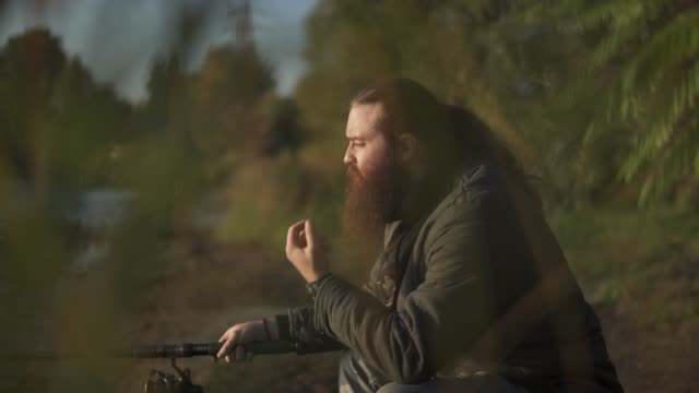Fisherman with long beard fishing on the river bank. Fisher strokes his beard. River fishing. Fisherman with long beard fishing on the river bank. Fisher strokes his beard. River fishing. fishing rod stock videos & royalty-free footage