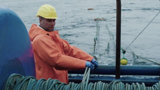 vídeos de stock, filmes e b-roll de pescador trabalha no navio de pesca comercial que arrasto puxa - países bálticos