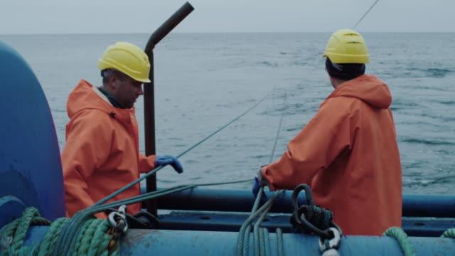 vídeos de stock, filmes e b-roll de o pescador trabalha no navio de pesca comercial que puxa a rede de trawl - países bálticos