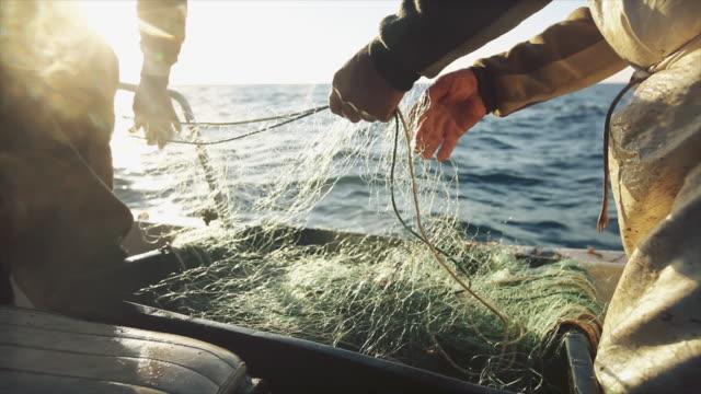fishermen at work on the fishing boat: pulling the nets - łowić ryby filmów i materiałów b-roll