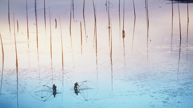 Fishermen carrying fish nets on artistic Mudflats beach in Xiapu, Fujian Province, China. video