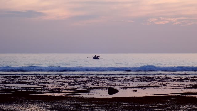 vídeos de stock e filmes b-roll de fishermen catch fish from the boat at low tide at sunset - fishman