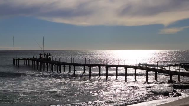 vídeos de stock e filmes b-roll de fishermen catching fish on the pier . sunlight reflection in coming waves seascape. - fishman