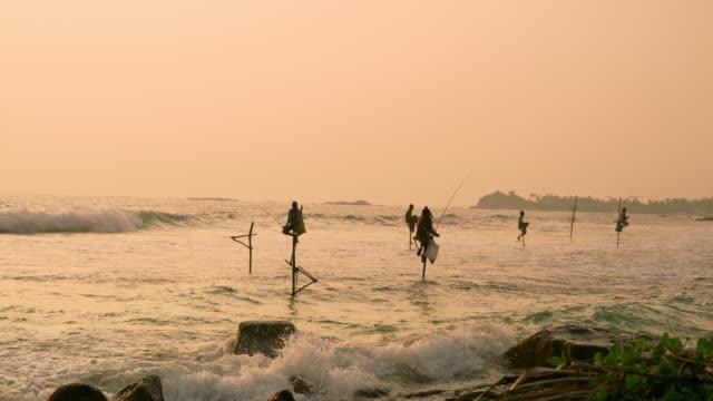 MS Fishermen fishing from posts over ocean at sunset,Sri Lanka