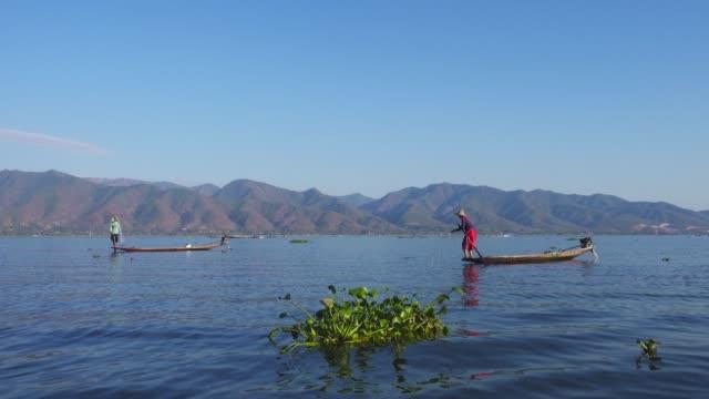 Fishermen in a canoe fishing on famous Inle Lake Fishermen in a canoe fishing in the famous Inle Lake, 4k myanmar stock videos & royalty-free footage