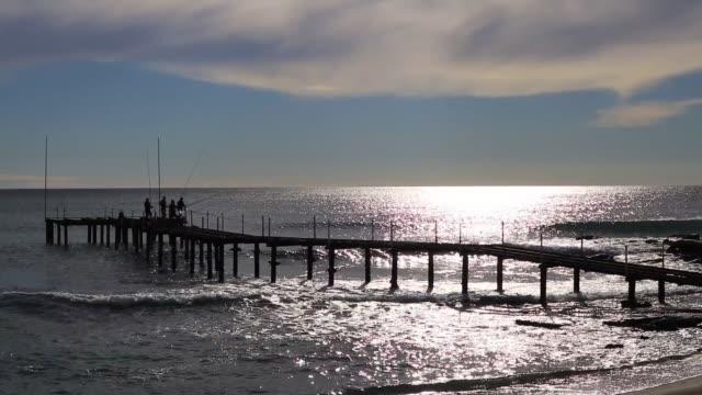 vídeos de stock e filmes b-roll de fishers on beach pier catching fish. sunlight reflection in coming waves seascape. - fishman