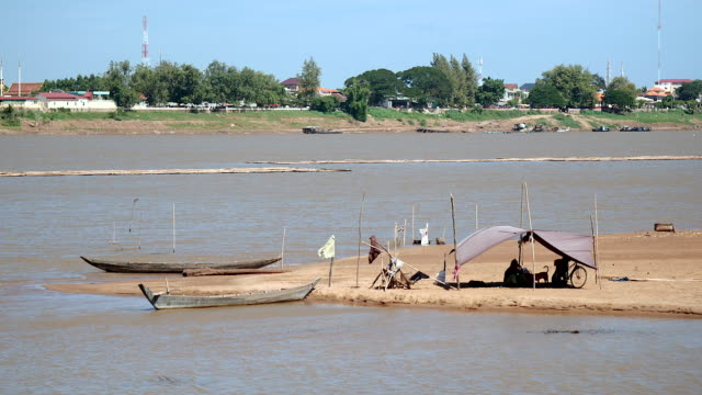 Fishers sitting under tarpaulin on river sandbank during windy day,