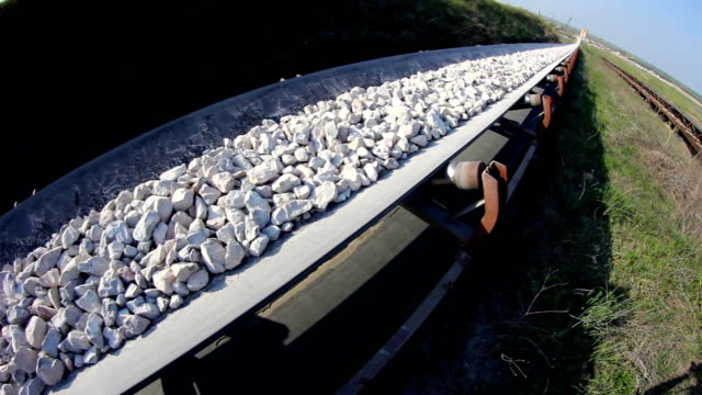 Fisheye of a conveyor belt transporting stones Fisheye of a long conveyor belt transporting stones to the manufacturing plant about 5 miles away. conveyor belt stock videos & royalty-free footage