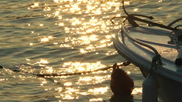 vídeos de stock e filmes b-roll de fishing boat and sun reflection on sea - vela desporto aquático