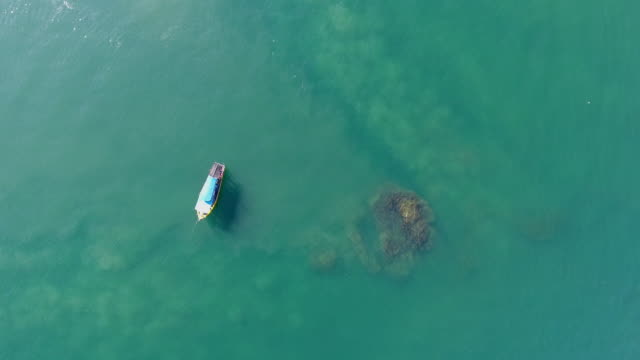 Fishing Boat in A Sea with Transparent Water, Aerial Video Alone fishing boat mooring in a sea with transparent water, aerial video. Flying in the morning. recreational boat stock videos & royalty-free footage