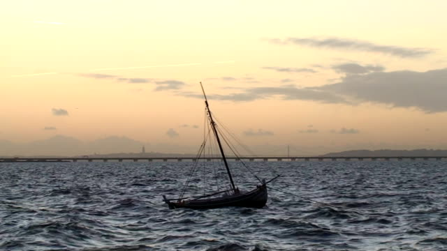Fishing boat in rough sea at sunset video