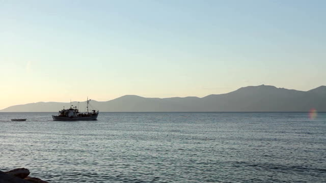 Fishing boat is in transport passing over sea at sunset video