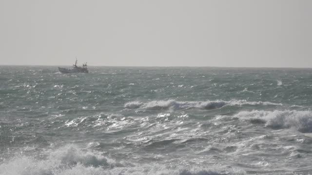 a fishing boat returns to port in a rough sea - погружённый стоковые видео и кадры b-roll