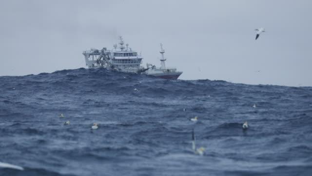 Fishing boat trawler sailing out at rough sea