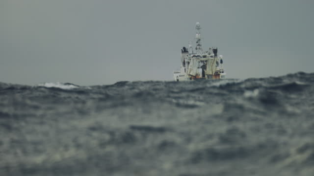 vídeos de stock e filmes b-roll de fishing boat trawler sailing out at rough sea - navio