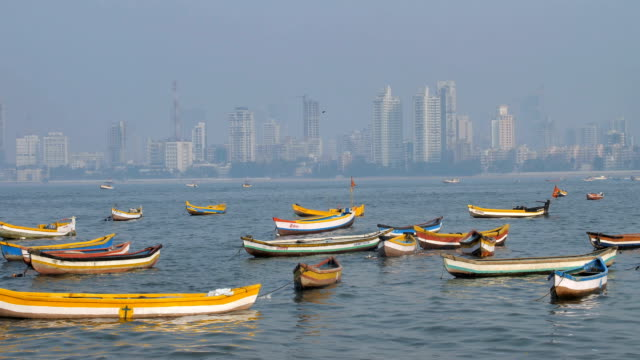 fishing boats are parked in the Arabian sea against the Indian city skyline video
