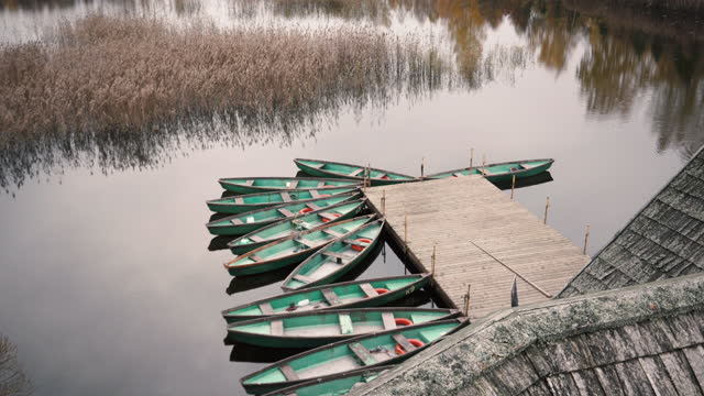 Fishing boats at the pier on the lake Green fishing boats at the pier near the house on the lake in autumn in October baltic countries stock videos & royalty-free footage