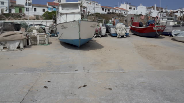 Fishing boats docked in harbor on a sunny day