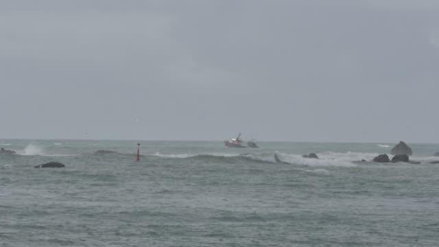 vídeos de stock, filmes e b-roll de 2 barcos de pesca retornam ao porto entre rochas - boia salva vidas
