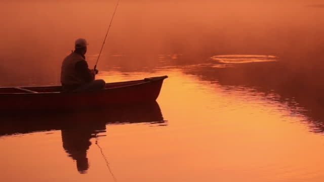 Fishing in lake at sunrise video