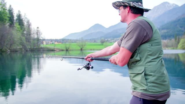 Fishing in the countryside and the man is throwing the bite in the lake on a nice day, footage in slow motion. video