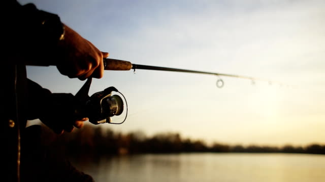 Fishing on the lake at sunset. A young man is fishing for spinning against the background of the setting sun. Silhouette of a fisherman. Hands close up.