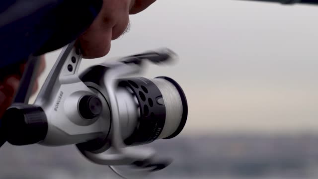 Fishing rod and swing Fishing with spinning on the sea. cloudy weather tying rope winter 4K view Galata bridge in istanbul Closeup of professional spinn fishing rod  tying rope winter fishing rod stock videos & royalty-free footage