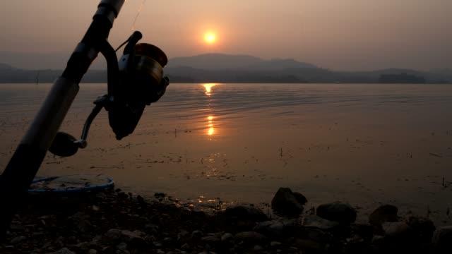 fischen stäbchen am ruhigen see bei beautiful sunrise - angelhaken stock-videos und b-roll-filmmaterial